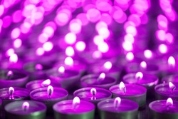 Purple pink candle light. Christmas or Diwali celebration tealight candlelight. Lit candles at night vigil. Close-up selective focus image of beautiful night light flames with blurred background.