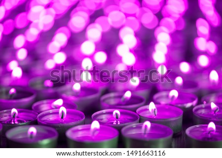 Photo of  Purple pink candle light. Christmas or Diwali celebration tealight candlelight. Lit candles at night vigil. Close-up selective focus image of beautiful night light flames with blurred background.