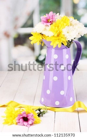 Purple pitcher of peas with flowers on wooden table on window background