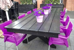 Purple plastic chairs in front of a wood table. Purple flowers in pink pots on this table. Empty brasserie in bad weather. Empty coffee shop terrace before opening. Purple background