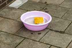 purple plastic round tub filled with soapy water and a sponge standing on the street