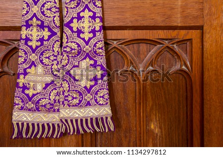 Purple priest stole used for confessions, vestment purple and gold as worn during confession and mass. - Shutterstock ID 1134297812