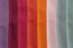 Purple, red, orange and blueish green tints of a set of comparison interior decoration sample swaps of textured curtain fabric with various shades and colors and colorful backdrop evenly lit