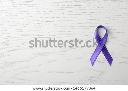 Purple ribbon on white wooden background, top view with space for text. Domestic violence awareness