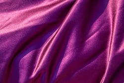 Purple satin background. Silk texture. Fabric pattern.