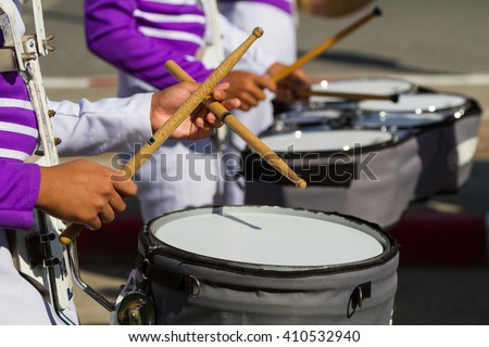 purple shirt musician in marching band playing drum with drumstick on band background