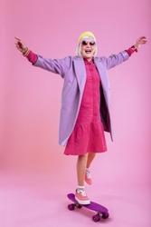 Purple skateboard. Fashionable retired woman wearing pink dress standing on purple skateboard