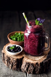 Purple smoothie with blackberry, basil, mint, dill and parsley on wooden rustic background