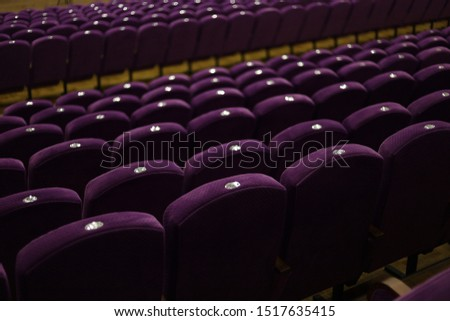 Purple soft velvet chairs in the theater hall #1517635415
