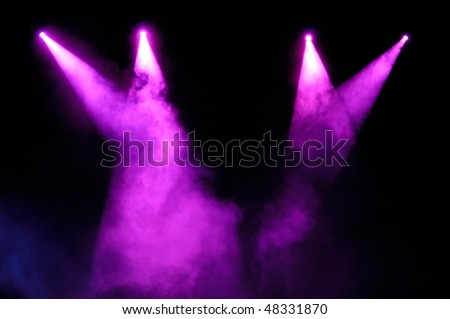 Purple stage spotlights in smoke over black background