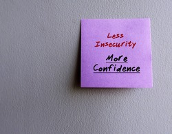 Purple sticky note on copy space grey wall written LESS INSECURITY, MORE CONFIDENCE concept of stop being insecure ,build up self-esteem by change mindset, overcome negative thought, affirm own value