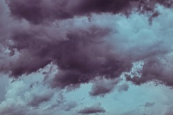 purple stormy clouds floating menacingly over a greenish sky.