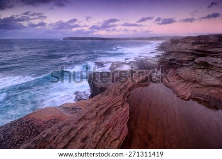 Purple sunrise from the cliff overlooking ocean and distant cliffs and beaches