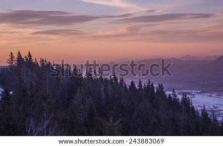 Stock Photo Purple Sunrise in the Hills & Forest. Snowy mountains on an early winter morning. Photograph was taken in Slovenia on the border with Austria. Panorama with forest, mountains, clouds and clear sky.