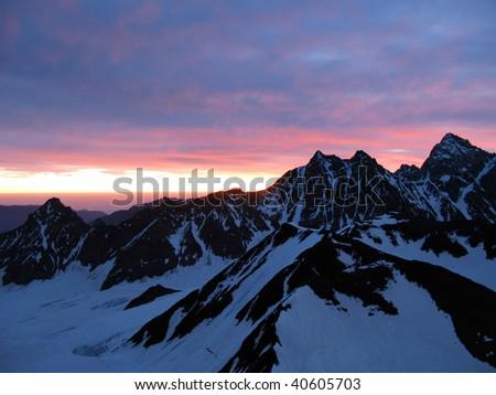 purple sunset at Lyalver mountain at Bezenghi Wall at Caucasus mountains - stock photo