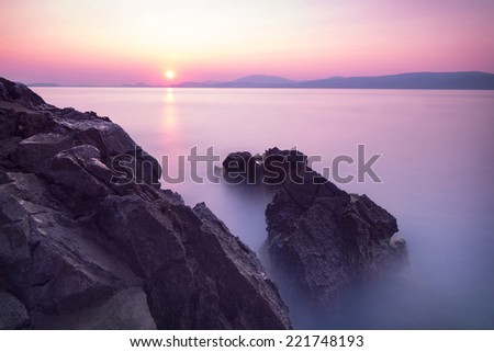 Purple sunset over sea, majestic rocks in the fog, beautiful beach landscape, wonderful panoramic scene in Europe, travel and tourism concept