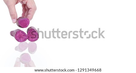 Purple sweet potato in hand asian woman isolated on white background and shadow; putting potato to take pictures.