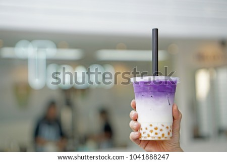 Purple sweet potato milk tea - Hand holding a glass of iced taro latte with boba or golden bubble on blurred background, Most Popular in Taiwan. #1041888247