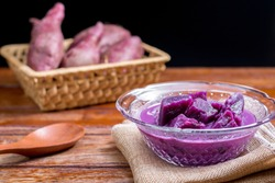 Purple sweet potato with coconut milk in transparent bowl on wooden table on black background. Delicious Thai dessert.