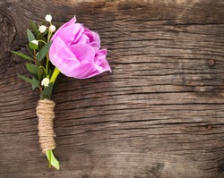 Purple tulip buttonhole for groom on the wooden background. Close up