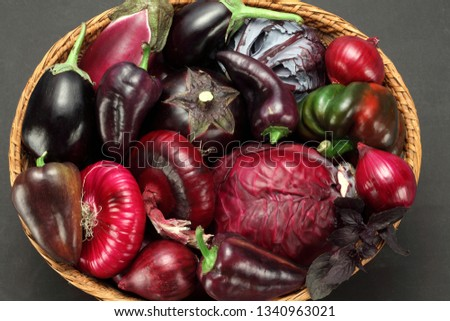 Purple vegetables basket: eggplant, red onion, red cabbage head, radicchio, purple bell pepper, basil