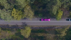 purple violet limousine driving fast along the forest road. in the autumn afternoon, a brightly colored long car rushes along the highway. view from above. top shot aerial view