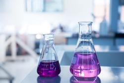 purple water solution in two size of glass flask in chemical blue science laboratory background