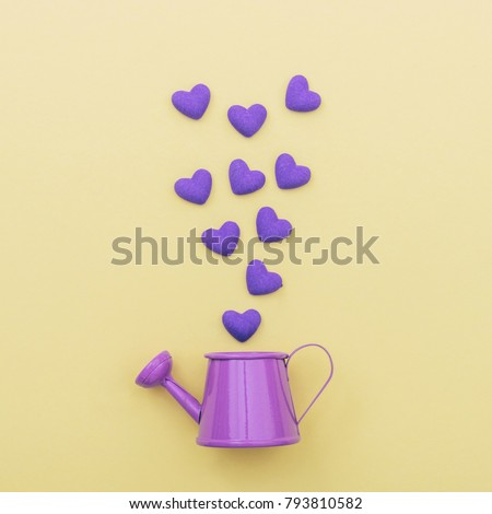 purple watering can for flowers from which fly hearts. minimal concept #793810582