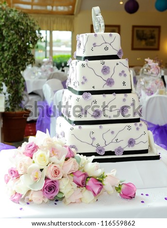 Purple wedding cake with brides bouquet at reception