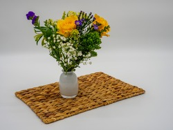 Purple, Yellow and Green floral arrangement in a white glass vase sitting on a brown whicker placemat with a white background.
