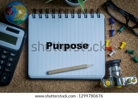 PURPOSE inscription written on book with globe,eyeglasses, calculator, camera, pencil and vase on wooden background with selective focus and crop fragment. Business and education concept Stock fotó ©