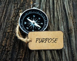 PURPOSE inscription written on paper tag, compass on old wooden background.