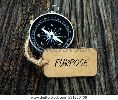 PURPOSE inscription written on paper tag, compass on old wooden background. Stockfoto ©