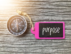 PURPOSE text written on paper tag with magnetic compass on old wooden background. A concept.