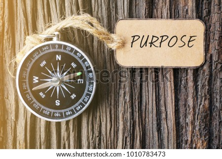 PURPOSE text written on paper tag with magnetic compass on old wooden background. A concept. Stockfoto ©