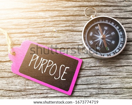 PURPOSE text written on wooden tag with magnetic compass on old wooden background. A concept. Stockfoto ©