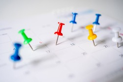 Push pins on calendar, mark the Event day with a red pin. Close-up of red pins.