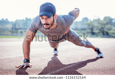 Push ups. Young muscular sportsman doing fitness exercise outdoors. Sport, fitness, street workout concept