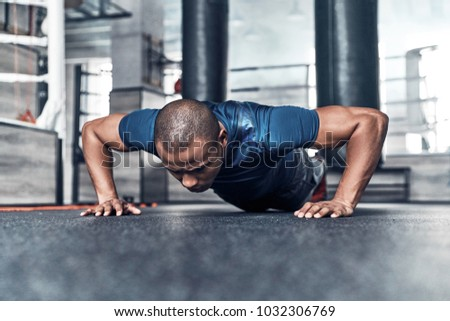 Pushing hard. Handsome young African man in sport clothing doing push-ups while exercising in the gym