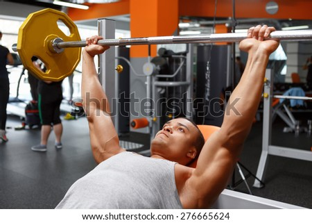 Pushing up.  Lying handsome powerful man lifting barbell in sport gym.