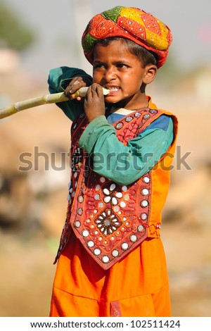 PUSHKAR, INDIA - NOVEMBER 7: An unidentified Rajasthani boy dressed in ethnic clothes enjoys sugarcane at the Pushkar cattle fair on November 7, 2011 in Pushkar, Rajasthan, India.
