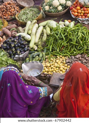 PUSHKAR, INDIA - NOVEMBER 10: Unknown Indian women selling fruit and veg on November 10, 2008 at a street market in Pushkar, Rajasthan, India