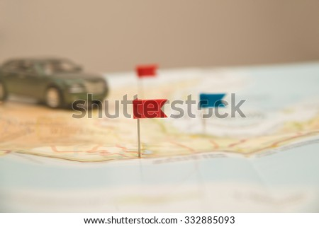 Pushpin and small, toy car on map for travel concept. pointing the location of destination point