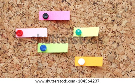 Pushpins holding blank note paper on a cork board.