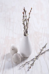 Pussy willow branches in vase with Easter egg on wooden kitche table. Easter table decoration.