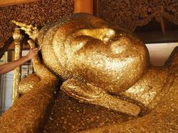 Put gold leaf onto the  Buddha image.big golden Buddha statue.