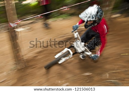 PUTRAJAYA, MALAYSIA - JANUARY 1: Panning shot of unidentified rider in a downhill mountain bike race during International Extreme Games 2012 in Putrajaya, Malaysia on January 1, 2012.