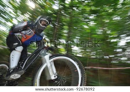 PUTRAJAYA, MALAYSIA - JANUARY 1: Panning shot of unidentified rider in a downhill mountain bike race during International Extreme Games 2012 in Putrajaya, Malaysia on January 1, 2012.