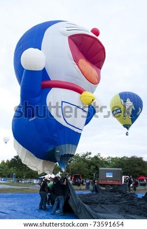 PUTRAJAYA, MALAYSIA-MAR 20:Doraemon balloon ready to liftoff at the 3rd Putrajaya International Hot Air Balloon Fiesta 20 Mar, 2011 in Putrajaya.7 special shape balloon in this year event - stock photo