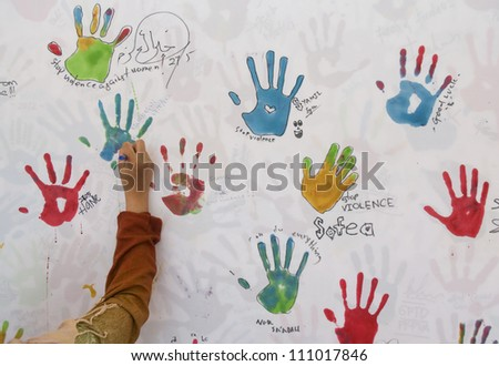 PUTRAJAYA, MALAYSIA - MAY 27: unidentified woman writes on the wall to show  support on stop violence against women campaign during National Youth Day 2012 on May 27, 2012 in Putrajaya Malaysia.